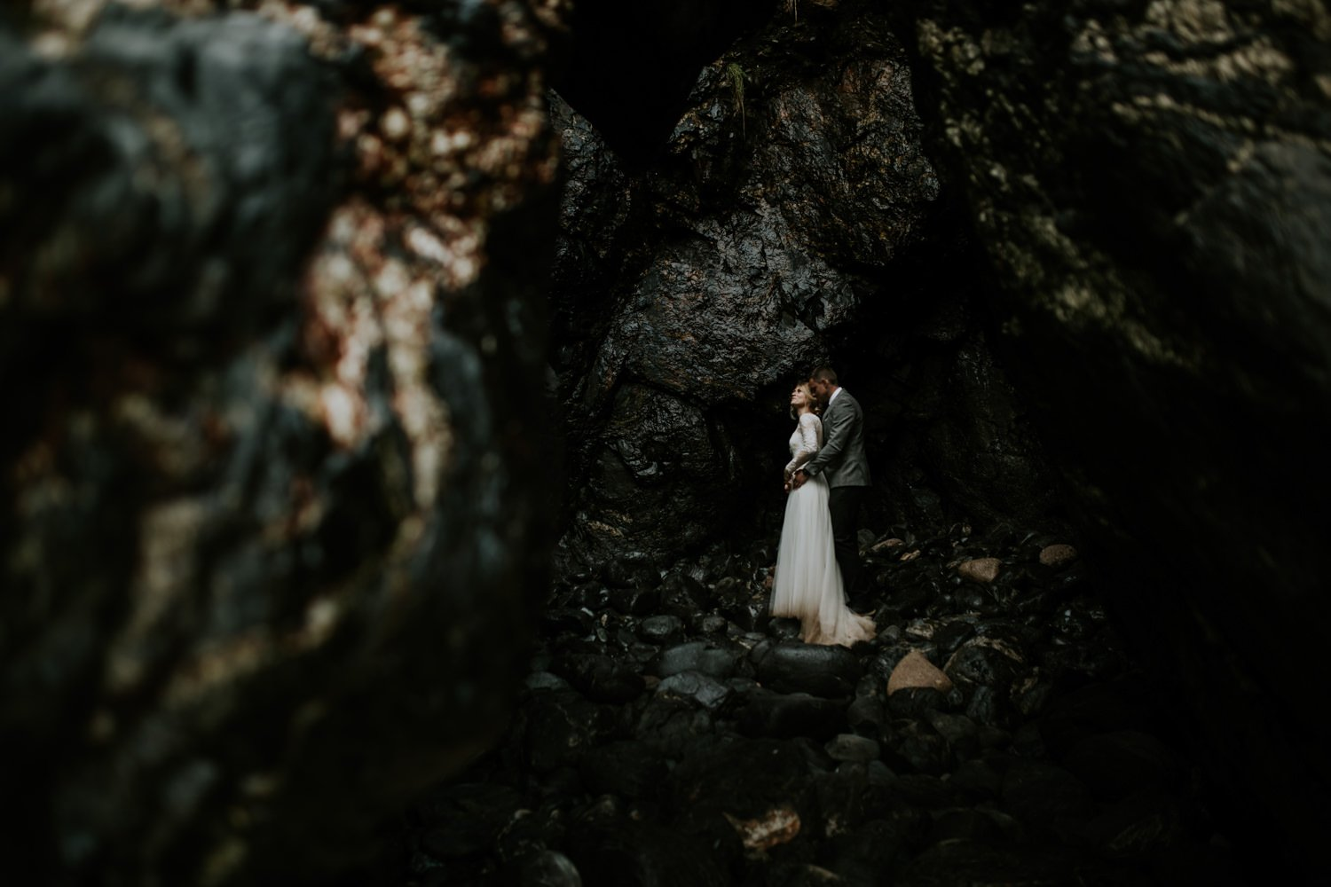 Iceland Elopements - Wedding Couple in Iceland cuddle in a sea cave in Vik